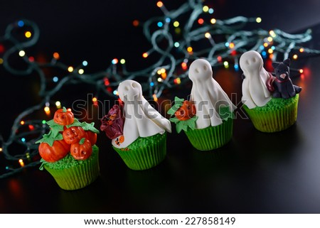 Row of Halloween cupcakes decorated with sugar ghosts and pumpkins. Diagonal framing. - stock photo