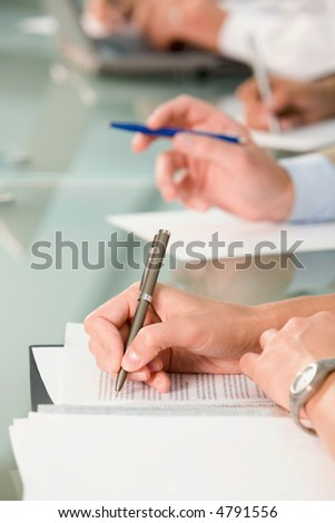 Row of hands holding pens and making notes