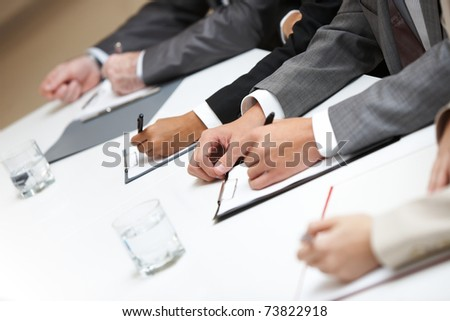Row of hands making notes - stock photo