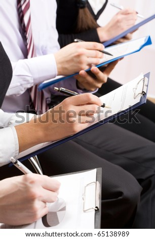 Row of hands making notes during a seminar - stock photo