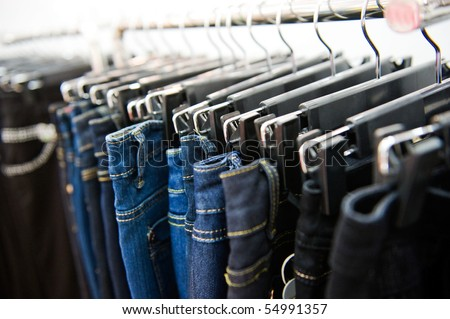 Row of hanged blue and black jeans in a shop - stock photo