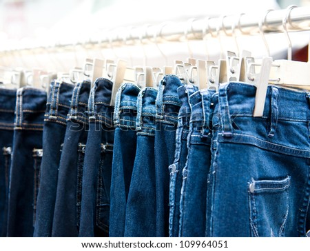 Row of hanged blue jeans in a shop - stock photo