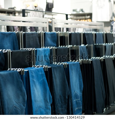 Row of hanged jeans in a shop - stock photo
