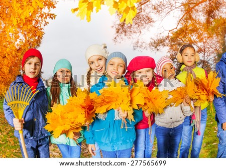 Row of happy cute kids with rake and bunch of yellow maple leaves standing close in row in the park during autumn daytime - stock photo