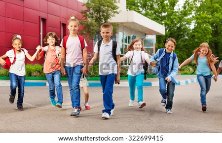 Row of happy kids with bags near school building - stock photo