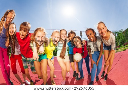 Row of happy teens standing on volleyball court - stock photo