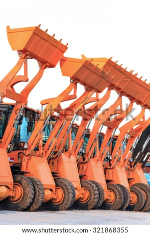 Row of heavy construction excavator machine against blue sky in  - stock photo