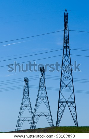 Row of high voltage power line towers on a hill