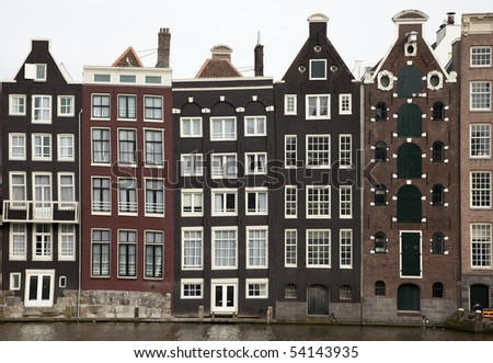 Row of historic houses located at the side of a canal, in Amsterdam, with the time having crooked the once straight lines of the architecture