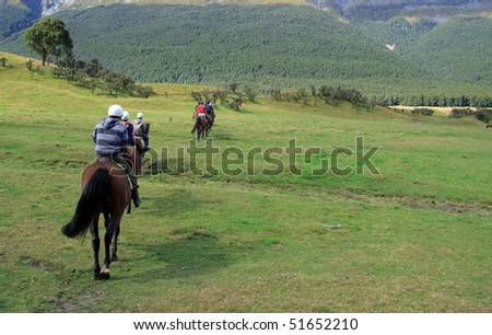 Row of horse riders in line going across a field - stock photo