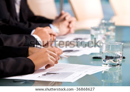 Row of human hands on workplaces with papers during conference