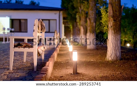 Row of Illuminated Outdoor Lights in Ground Alongside Stone Patio Furnished with Wooden Benches and Plaid Blankets Creating a Cozy and Inviting Atmosphere - stock photo