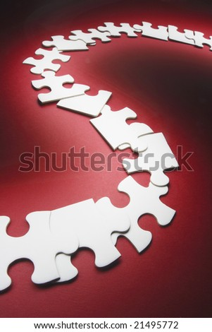 Row of Jigsaw Puzzle Pieces on Red Background