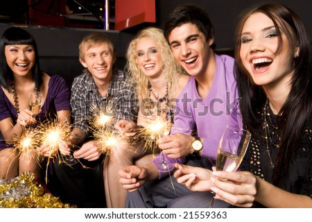 Row of joyful friends with champagne and xmas lights celebrating New Year - stock photo