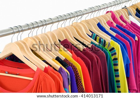 Row of l female clothes of different colors on hangers