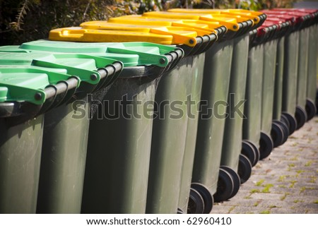 Row of large green wheelie bins for rubbish, recycling and garden waste - stock photo