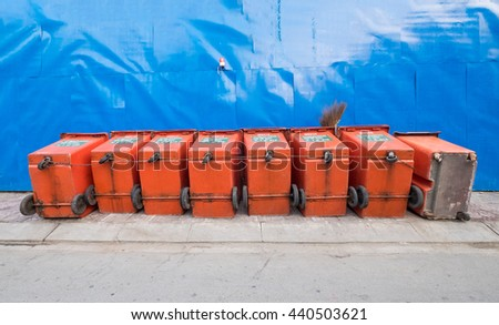 Row of large wheelie bins for rubbish, recycling and general waste. They are used by public cleaning organisations and locked by the chain and locker. - stock photo