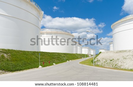row of large white tanks for petrol and oil in the Amsterdam harbor - stock photo