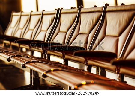 Row of leather chairs in international airport terminal at window background with yellow sunlight.