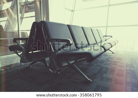 Row of leather chairs in international airport terminal by the window  - stock photo