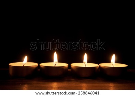 Row of lit candles in the dark - stock photo
