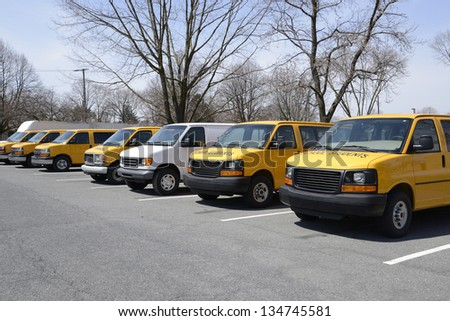 row of many yellow and white vans used to transport students to and from school - stock photo