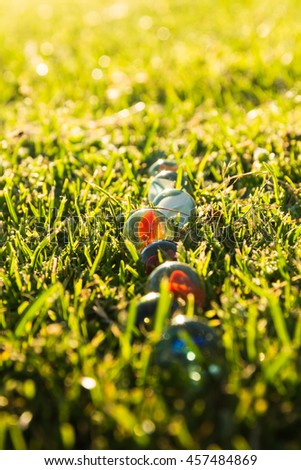 Row of marbles in the grass. Bright colors in summer. - stock photo
