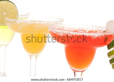 Row of Margarita cocktails in chilled salt rimmed glass with tequila, triple sec, juice, simple syrup and crushed ice. Classic icy party drinks served from a blender isolated on white background - stock photo