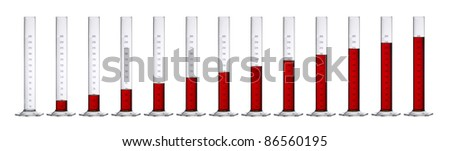 row of measuring cylinders made of glass, gradually filled with translucent red fluid in front of white back - stock photo