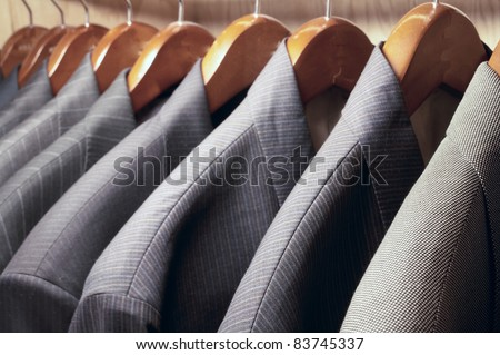 Row of men's suit jackets hanging in closet - stock photo