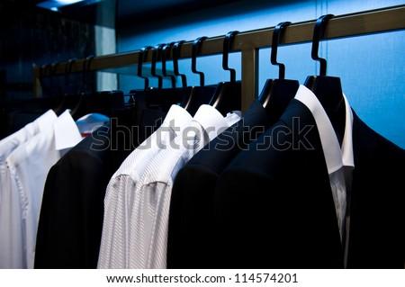 Row of men's suits hanging in closet. - stock photo