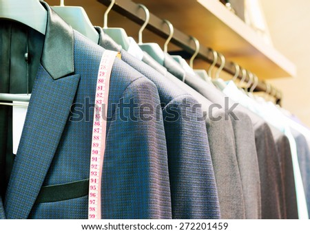 Row of men's suits hanging in closet. - stock photo