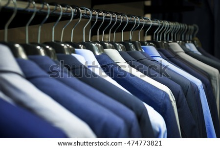 Row of men's suits hanging in closet.