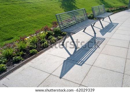 row of metal park benches with green grass behind - stock photo