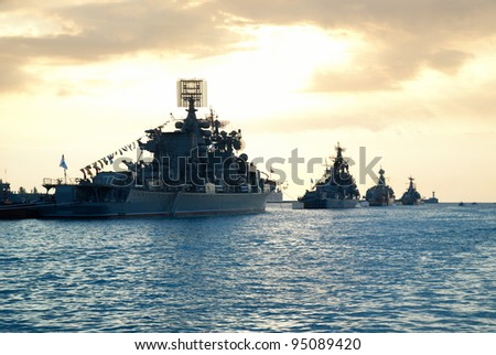 Row of military ships against marine sunset - stock photo