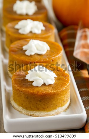 Row of mini pumpkin pies with whipped cream sitting on white platter with orange checkered napkin and fresh pumpkin in background