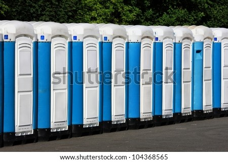 Row of mobile toilets in a summer festival area - stock photo