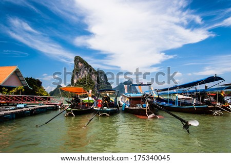 Row of moored long-tail boats in front of limestone karsts at Koh Panyee floating fishing village, Phang Nga Bay, southern Thailand