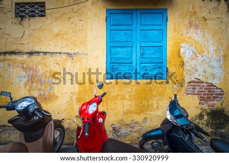 Row of motorbikes parked near building with yellow grungy wall. Scooter parking in street, Vietnam. City life with convenient and fast vehicle. Popular means of transport in Asian countries.