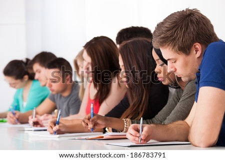 Row of multiethnic college students writing at desk in classroom