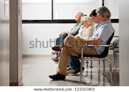 Row of multiethnic people sitting side by side while waiting for doctor in hospital lobby - stock photo