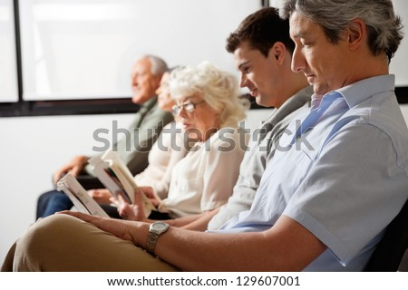 Row of multiethnic people waiting for the doctor in hospital lobby - stock photo