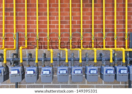 Row of natural gas meters with yellow pipes on building brick wall - stock photo
