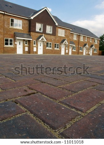 Row of new red brick terraced houses with cobbled pavior street in foreground, UK. - stock photo