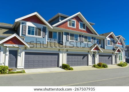 Row of new residential townhouses on a street on sunny day. Family townhouses with concrete driveways and asphalt road in front. British Columbia, Canada. - stock photo
