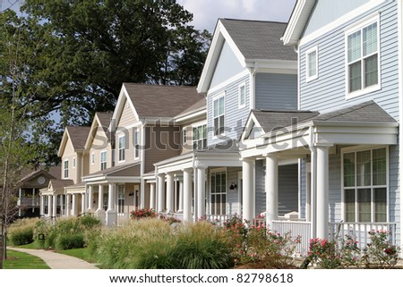 Row of newly constructed townhomes in a sidewalk neighborhood. - stock photo