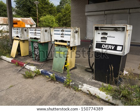 row of old badly decayed fuel pumps - stock photo
