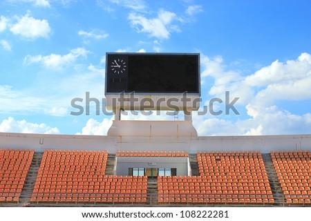 row of orange seats and score board in stadium - stock photo