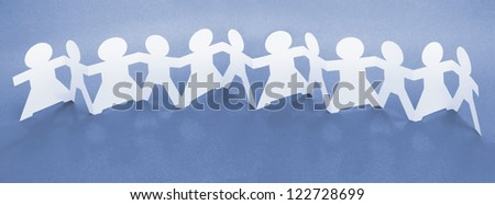 Row of Paper Chain Dolls Holding Hands on Blue Background - stock photo