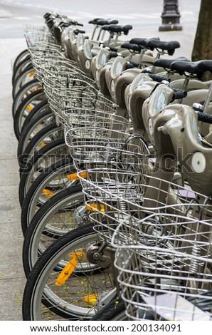 Row of parked bicycles for rent in the street of a modern European city - stock photo